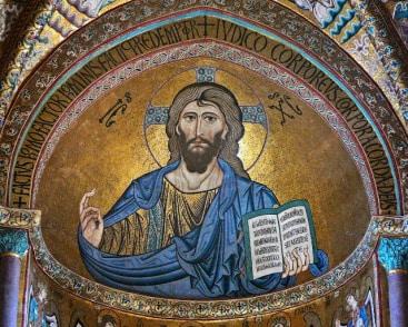"""Imagen de Cristo sentado en su trono, con la mano derecha en actitud de bendecir y sosteniendo en la mano izquierda el libro de los Evangelios. """"el pantocrátor es característico del arte románico y del bizantino y generalmente está enmarcado dentro de una aureola ovalada"""""""